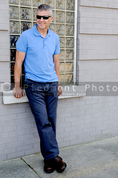 A man standing and leaning up against a building
