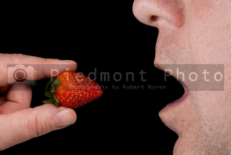 A man eating a fresh and delicious strawberry