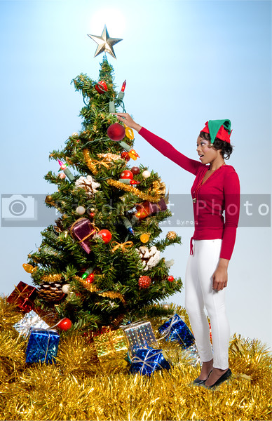A beautiful young black woman holding a Christmas present