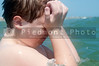 A young boy swimming in the ocean rubbing his salt water saturated eyes