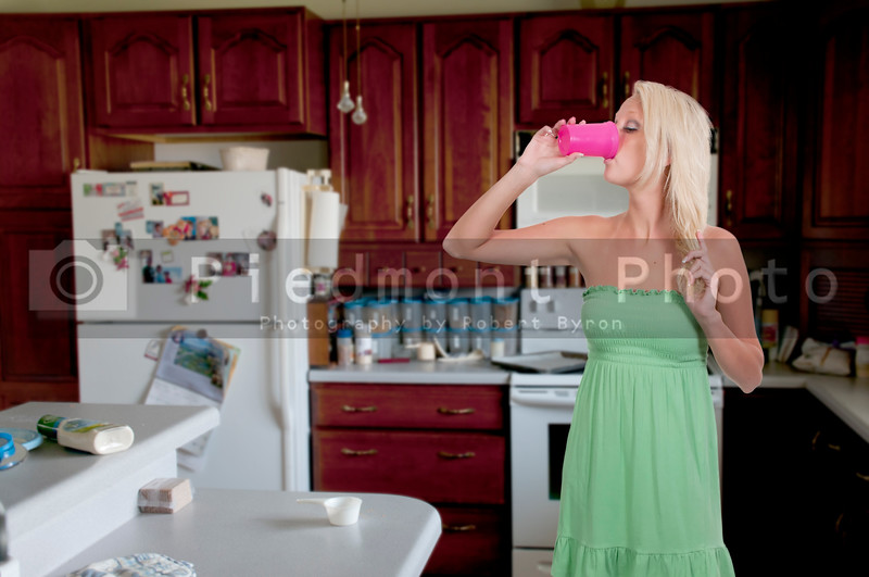 A beautiful young woman drinking juice or milk or water in the morning
