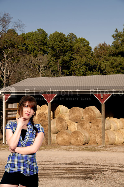 A beautiful young woman in front of a barn with bales of wheat hay.