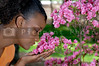 A young black woman stopping to smell the flowers