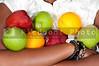 A black woman holding an assortment of fruit