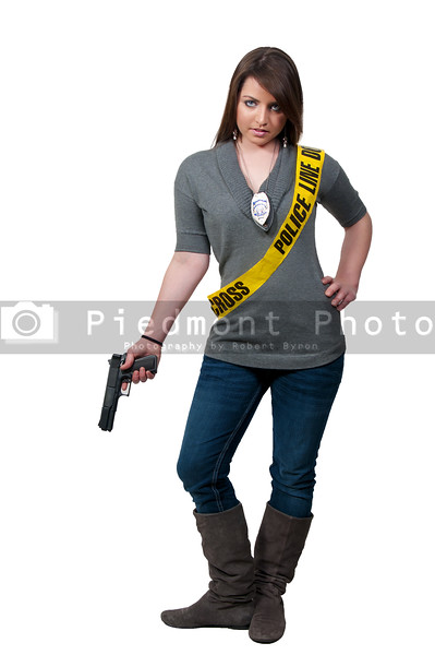 A young and beautiful woman holding a handgun wearing police line tape as a sash