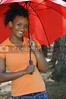 A beautiful young black woman holding an umbrella