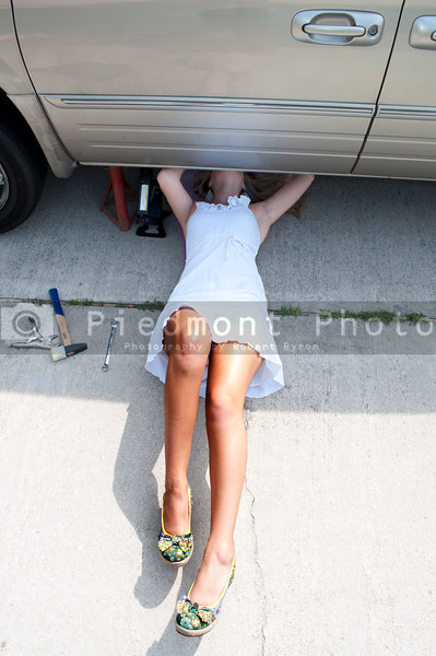 A beautiful female mechanic working on an automobile