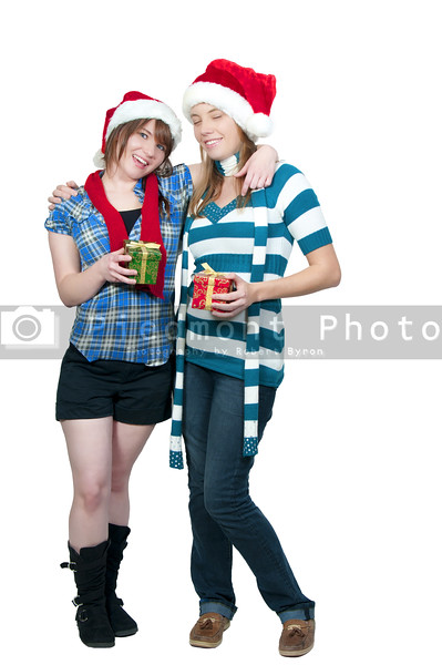 A couple of beautiful young women exchanging Christmas presents