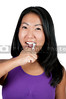 A beautiful Asian woman practicing good oral dental care by brushing her teeth