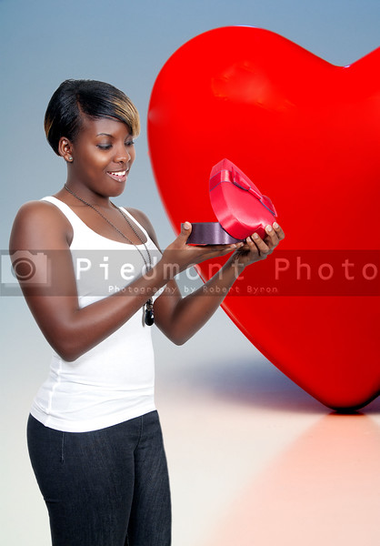 A beautiful young black African American woman holding a Valentines Day heart box gift present