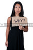 A beautiful young Asian woman holding up a sign that says why