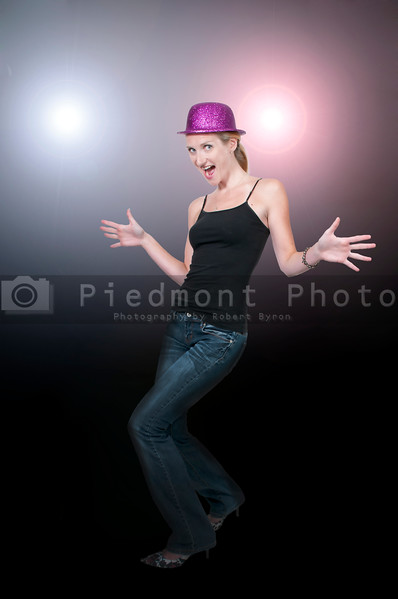 A woman in front of stage lights dancing caberet style