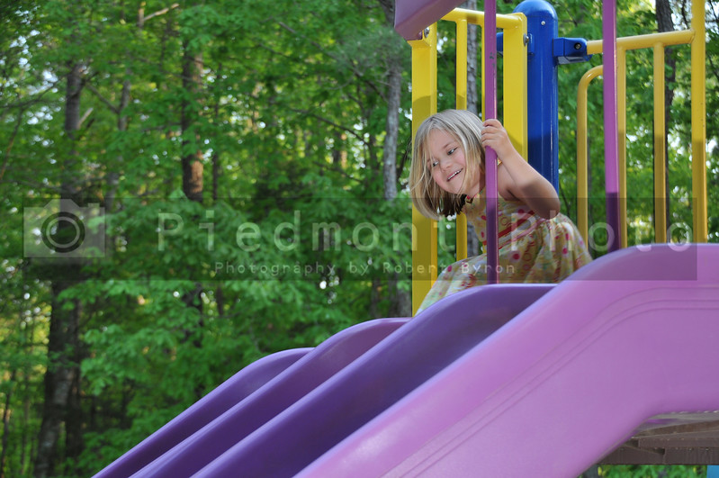 A young girl on a slide at a park