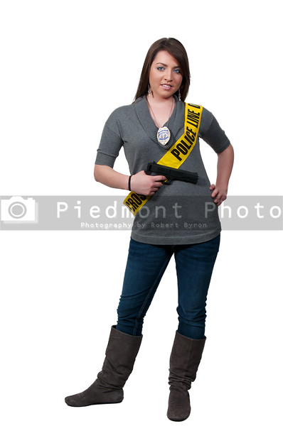 A young and beautiful woman police detective holding a handgun wearing a police line sash