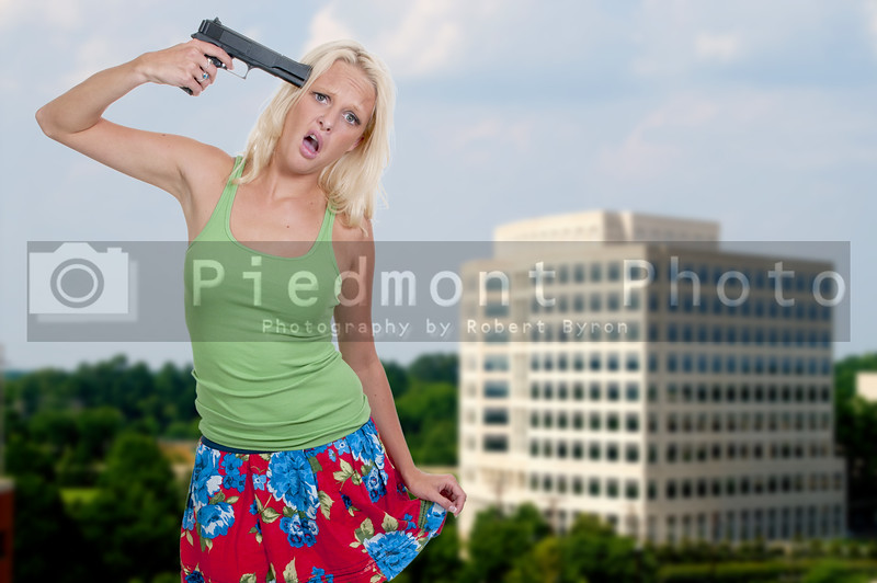 A beautiful woman holding a gun to her head threatening suicide