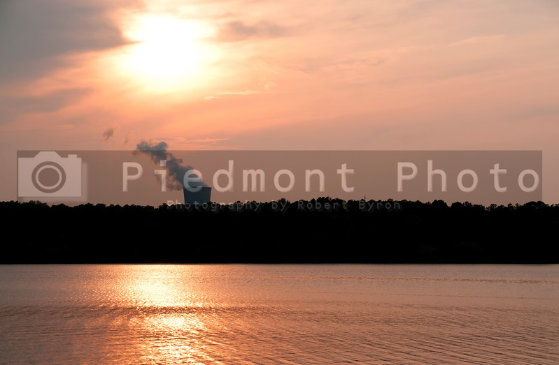 A functioning nuclear power plant on a lake at sunset.