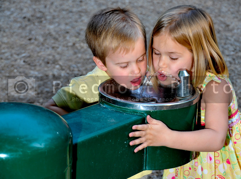 Kids drinking water from a public fountain