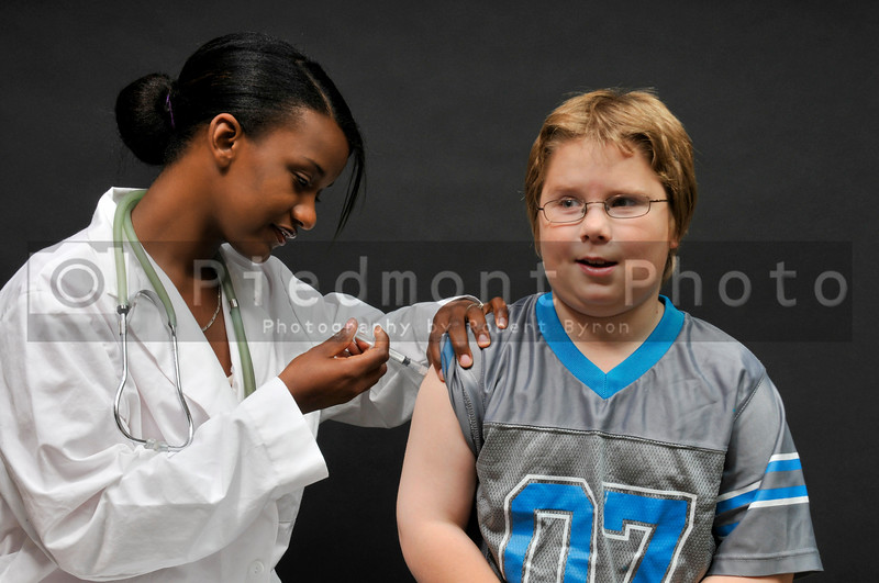 A female doctor giving a young boy a shot