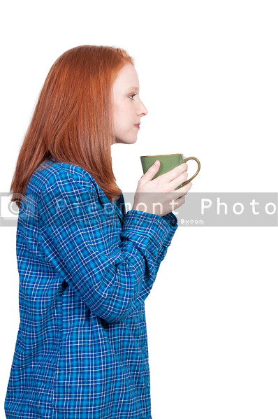A beautiful young Asian ethnic woman drinking coffee in her pajamas