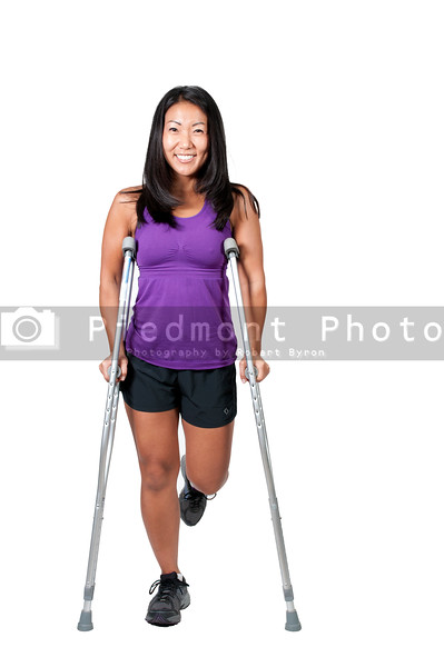 A beautiful Asian woman using a set of medical crutches to help her walk