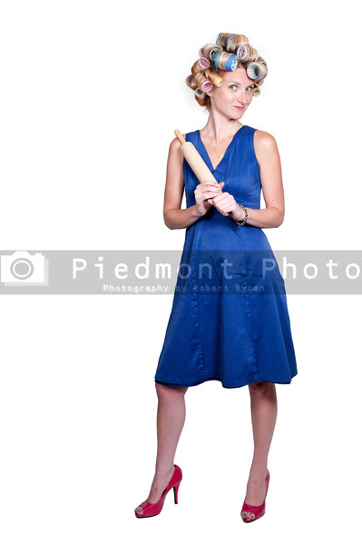 A beautiful young woman with curlers in her hair holding a rolling pin