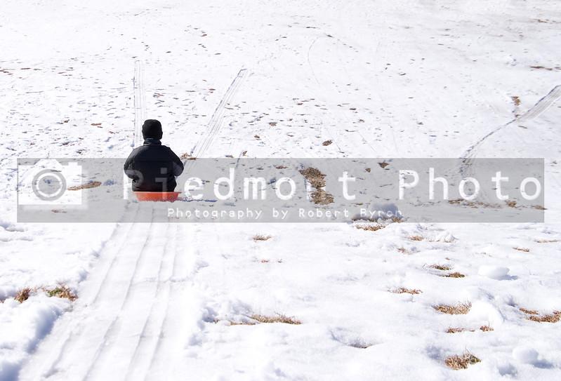 A young boy sledding down a hill