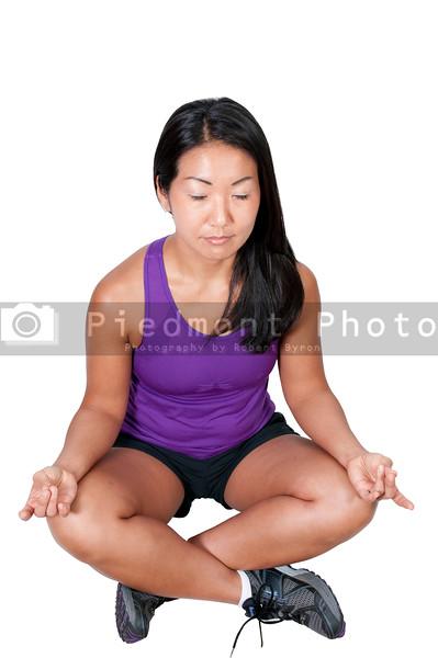 A beautiful Asian woman doing her Yoga lotus position execises