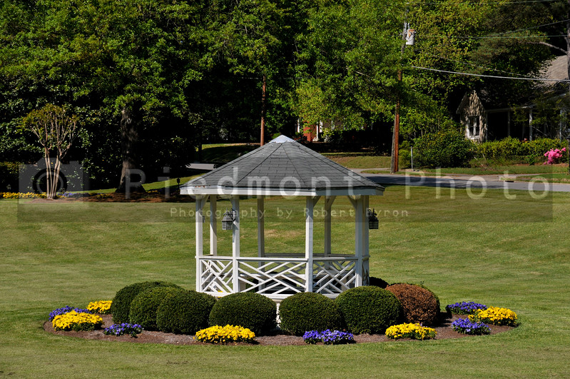 A gazebo in a front yard with flowers