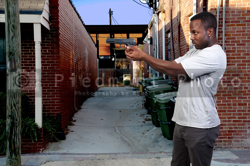 A black African American police detective man on the job with a gun