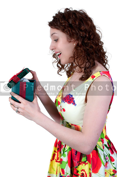 A beautiful young woman opening a birthday present