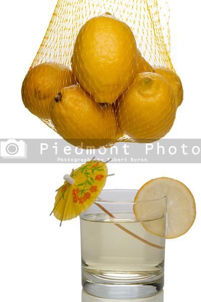 A bag full of bright yellow lemons and lemonade