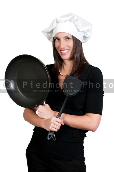 A beautiful young woman chef holding a spatula and frying pan