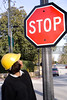A Female Construction Worker looking at a stop sign