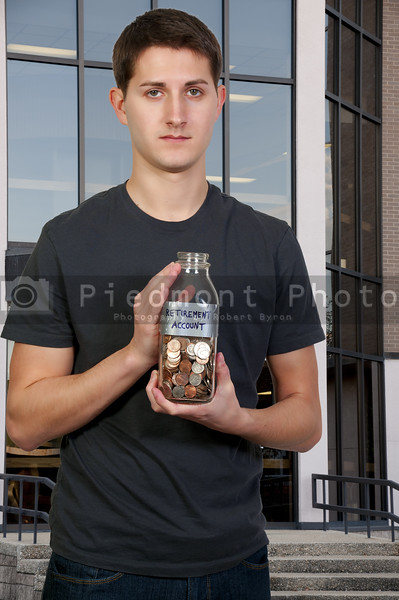 A young man holding a jar of money coins labeled retirement acount