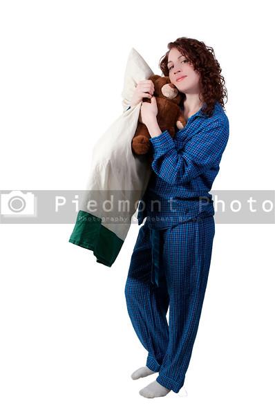 A beautiful young woman wearing pajamas hugging her stuffed teddy bearand a pillow