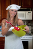 A beautiful woman chef holding a salad bowl and tongs