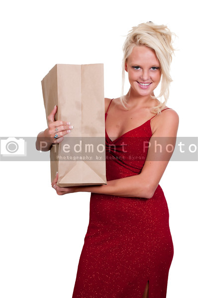 A beautiful young woman on a grocery shopping spree holding a brown paper bag