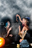 Beautiful young women witches with a snake in a jack-o-lantern