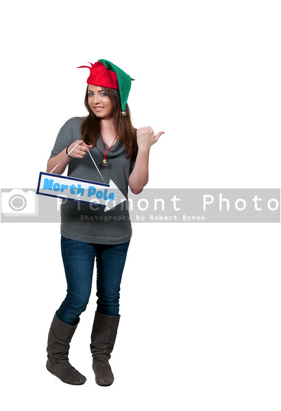 a beautiful black woman elf holding a north pole sign