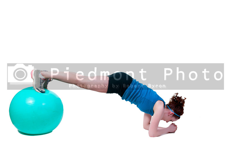 A beautiful young woman working with an aerobic exercise ball