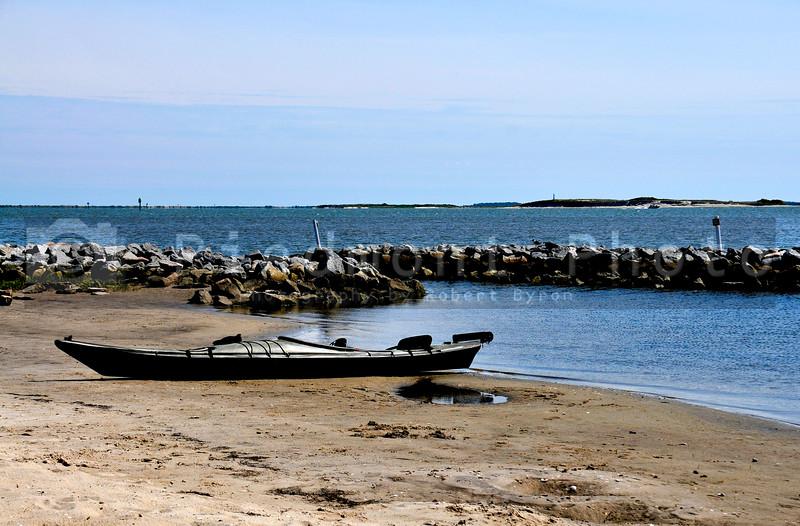 A Black Kayak on a sandy beach