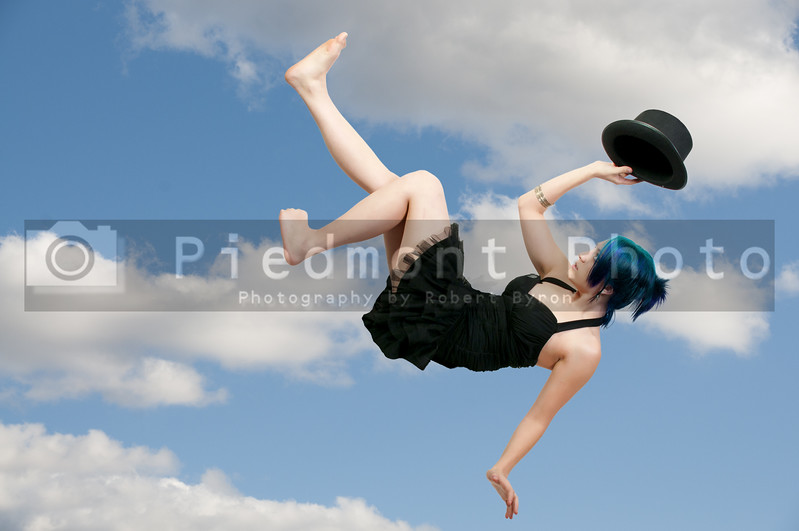 A beautiful young actress dancer wearing a top hat flying through the air