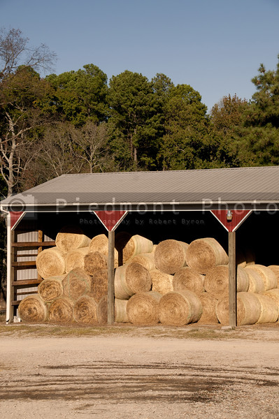 A barn with bales of wheat hay.