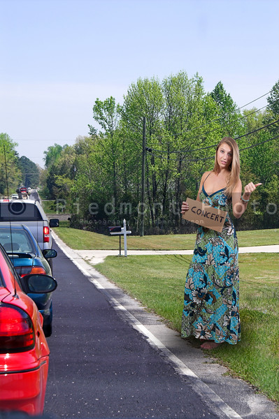 A beautiful woman with a sign hitch hiking to a concert