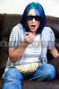 Beautiful young woman watching a 3d dvd movie on tv at home with popcorn