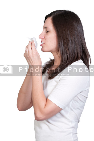 A beautiful woman with a cold, hay fever or allergies blowing her nose