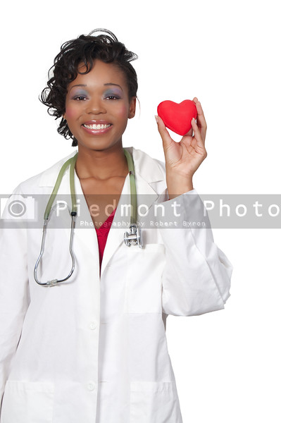 A beautiful female doctor in a lab coat holding a heart