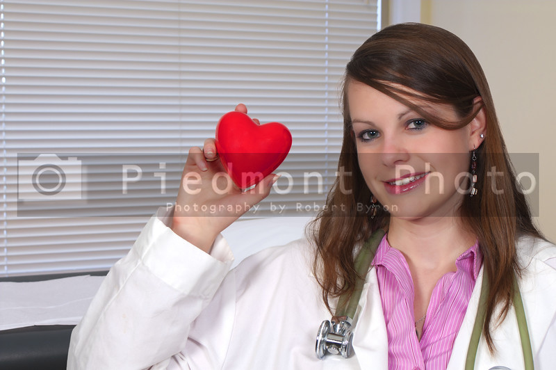 A female cardiologist office with a woman doctor holding a red heart in an exam room