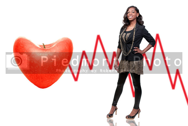 A beautiful young African American black teenage woman standing next to a heart shaped apple.
