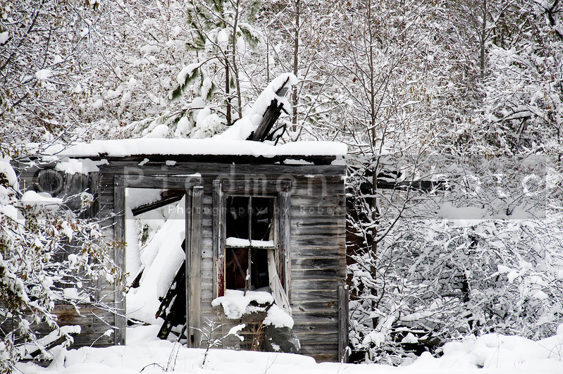 Ghost image in the window of an old abandoned collapsed building covered in a winter snow storm